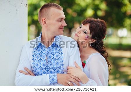 Ukraine. Happy Ukrainian wedding bridal couple in the ukrainian style. Beautiful bride and groom in the ukrainian style are standing with bouquet. Female and male models. Outdoor. park summer outdoor