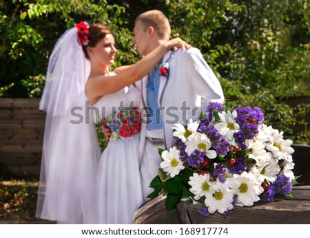 Ukraine. Happy ukranian wedding (bridal) couple in the ukrainian style.  Beautiful bride and groom in the ukrainian style are standing with bouquet. Female and male models. Outdoors, close up.