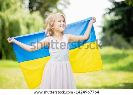 Ukraine's Independence Day. Flag Day. Constitution day. Child carries fluttering blue and yellow flag of Ukraine in field. Girl in traditional embroidery with flag of Ukraine