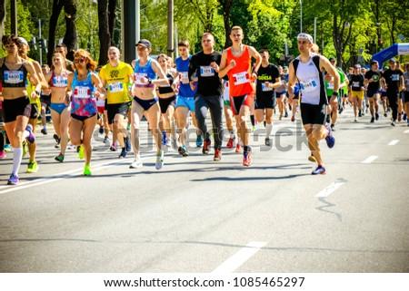 Ukraine, Vinnitsa April 28 2018 , Khmelnytsky highway : The half-marathon. Marathon running race people competing in fitness and healthy active lifestyle feet on road #1085465297