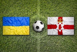 Ukraine vs. Northern Ireland flags on green soccer field