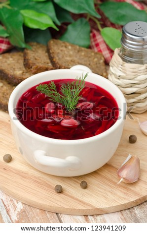 Ukrainian and russian national red borsch with herbs on a wooden board
