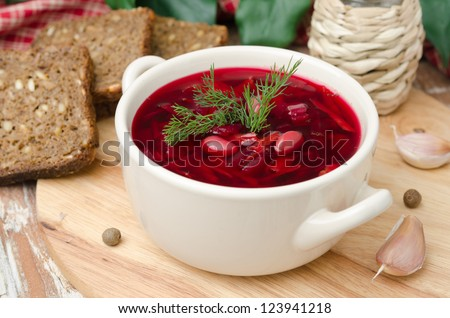 Ukrainian and russian national red borsch with herbs on a wooden board horizontal