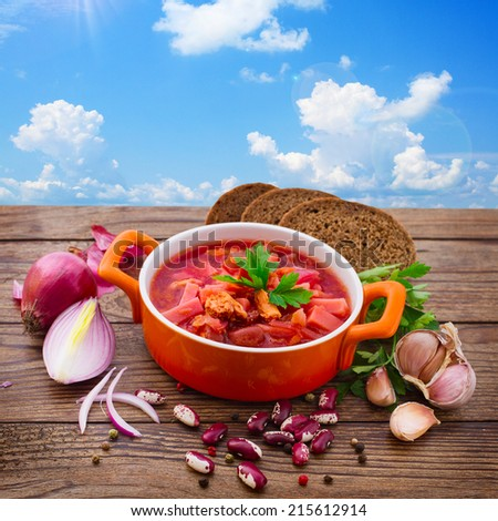 Ukrainian and Russian national Red Borscht with Bread closeup on Old Wooden Surface.  Soup for lunch. Food, meat, spices for cooking meat. Free space for text.