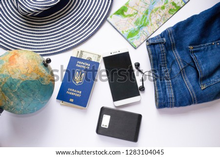 Ukrainian biometric passport with dollars for traveling. Power bank, smartphone, headphones, hat, jeans and map for valise packing.