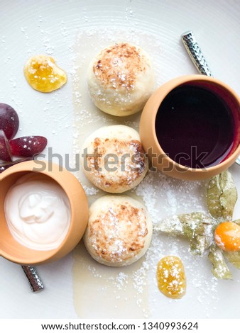 Ukrainian curd pancakes (syrniki, russian syrniki) on the plate with jam and sour cream. High resolution picture perfect for cooking book, receipt book or food magazine.