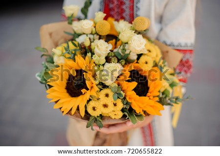 Ukrainian girl hands with a pretty little bouquet of beautiful yellow sunflowers no face close up #720655822
