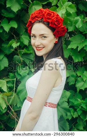 Ukrainian girl in a shirt and a wreath of flowers and ribbons on his head on a background of green grass