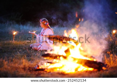 Ukrainian girl with a wreath of flowers on her head against a background of fire