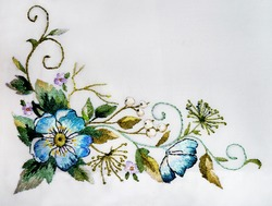 Ukrainian hand embroidery on fabric. Embroidered blue flowers. Ethnic art satin stitch embroidery.