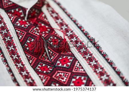 Ukrainian handmade vyshyvanka shirt embroidered with red and black threads. National clothing of Ukraine. Close up shot.  Сток-фото ©