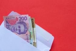 Ukrainian hryvnia in denomination of 200 lie in a white envelope on a red background close up