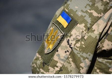Ukrainian soldier wearing military uniform with flag and chevron depicting trident - Ukrainian emblem and national symbol Foto d'archivio ©