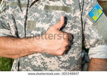 Ukrainian soldier with chevron on the uniform, focus on hand Stock fotó ©