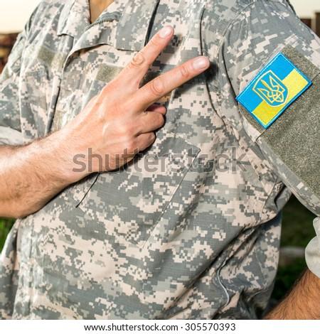 Ukrainian soldier with chevron on the uniform, focus on hand and chevron Stock fotó ©