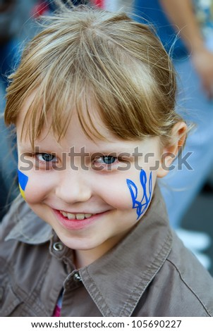 Ukrainian trident on the cheek of small girl