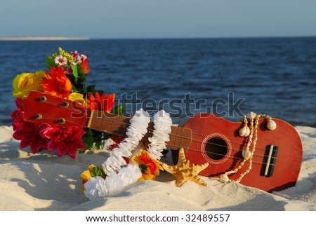 Ukulele and tropical items on beach ready for vacation