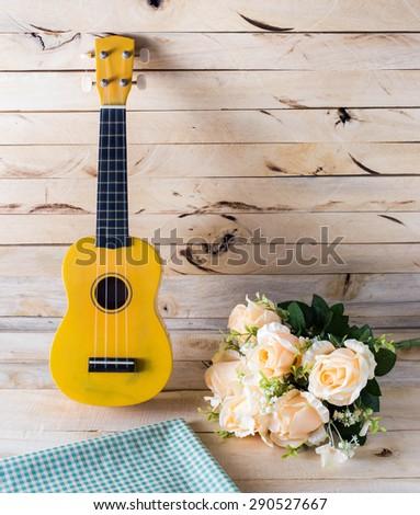 ukulele guitar with rose on wood background