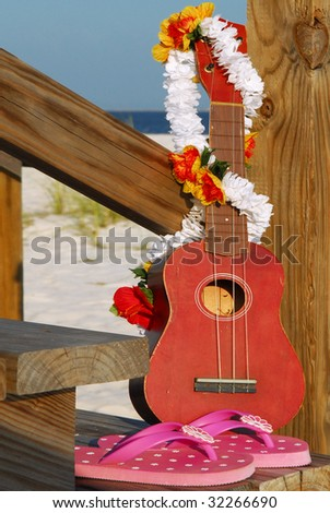 Ukulele instrument on beach by pretty fllipflops and lei
