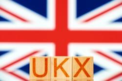 ukx index concept. wooden blocks with ukx lettering on british flag background