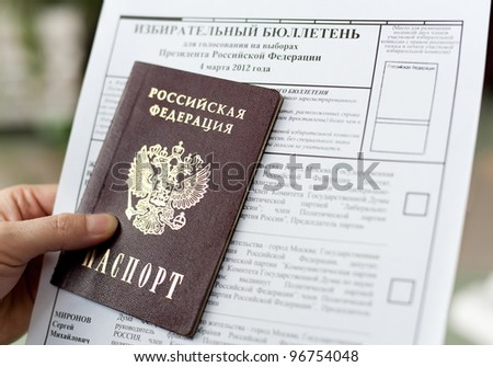 ULAN-UDE, RUSSIA - MARCH 4: A hand holds a passport and blank ballot for voting at the presidential election of Russia on March 4, 2012 at a local polling station, Ulan-Ude, Buryatia, Russia. - stock photo