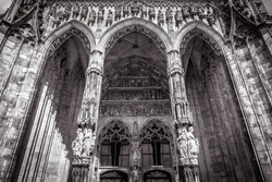 Ulm Minster or Cathedral of Ulm city, Germany. It is top landmark of Ulm. Front view of ornate entrance of old Gothic cathedral, luxury facade of famous medieval Christian church in black and white.