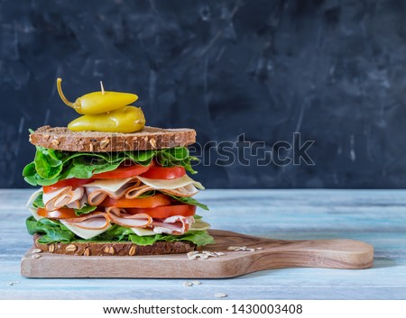 Ultimate deli or club sandwich with turkey pastrami lettuce and tomatoes on grey background with copy space Stok fotoğraf ©