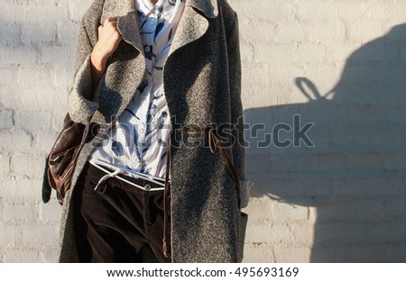 Ultra-fashion concept. young woman of fashion wearing gray coat and posing over white background. Street style. businesswoman. outdoors. fashionable accessories. #495693169