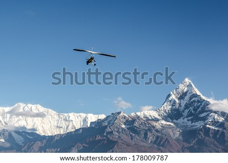 Ultra light plane flying over the Annapurna mountain range in the Himalayas near Pokhara, Nepal. The summit on the right is the Machapuchare (6993m), aka the fishtail mountain. #178009787