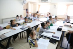 Ultra orthodox hasidic school children sit in their classroom at their desks and listen to their teacher, blurred