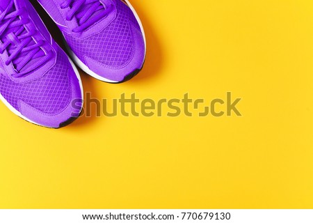 Ultra Violet sneakers on yellow background. Concept of healthy lifestile and food, everyday training and force of will. Color of the year 2018.