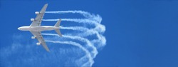 Ultra wide zoom photo of passenger airplane leaving white smoke trails in deep blue sky while flying at high altitude