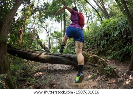 Ultramarathon runner cross country trail running in summer tropical rainforest