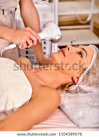 Ultrasonic facial treatment on ultrasound face machine. Woman receiving electric lift massage at spa salon. Electronic stimulation female muscles microcurrent therapy. Removal of pigmented spots. #1104389078
