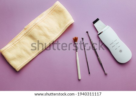 ultrasonic scrubber, cosmetic peeling brush uno spoon lies on a purple background . flat lay, the concept of cosmetology and tools Foto stock ©