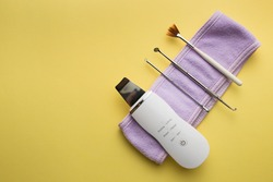 ultrasonic scrubber, cosmetic peeling brush uno spoon lies on a yellow background . flat lay, the concept of cosmetology and tools