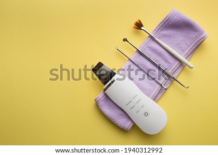 ultrasonic scrubber, cosmetic peeling brush uno spoon lies on a yellow background . flat lay, the concept of cosmetology and tools Foto stock ©