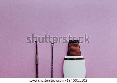 ultrasonic scrubber spoon uno lies on a purple background . flat lay, the concept of cosmetology and tools Foto stock ©