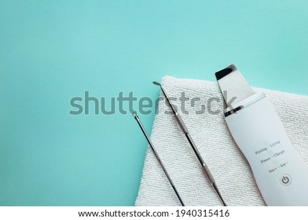 ultrasonic scrubber, uno spoon lies on a soft blue background . flat lay, the concept of cosmetology and tools Foto stock ©