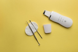 ultrasonic scrubber, uno spoon lies on a yellow background . flat lay, the concept of cosmetology and tools