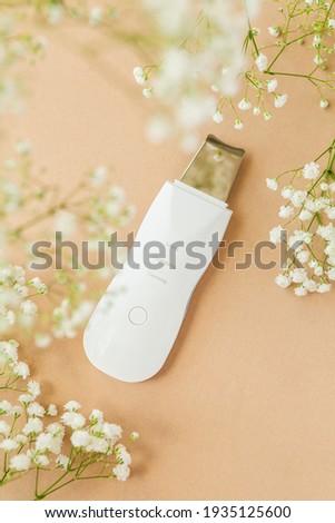 Ultrasonic Skin Scrubber Exfoliating Wand on tan background with babies breath flowers Stok fotoğraf ©