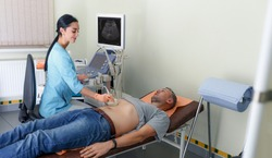 Ultrasound diagnosis of the stomach on the abdominal cavity of a man in the clinic, close-up view. The doctor runs an ultrasound sensor over the patient's male abdomen and looks at the image on the