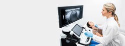 Ultrasound diagnostics of the thyroid gland. Woman endocrinologist making ultrasonography to a female patient in an ultrasound office of a modern clinic. Web banner