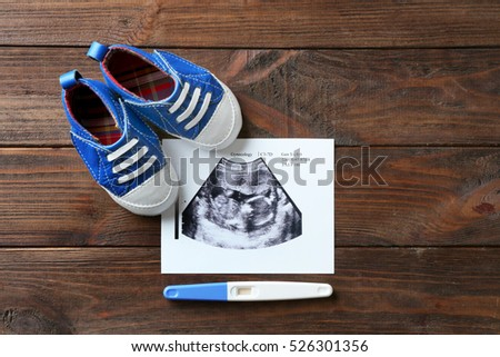 Ultrasound picture of baby, pregnancy test and children shoes on wooden background