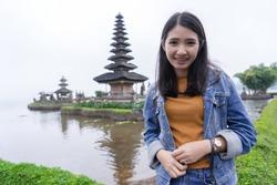Ulun Danu temple Beratan Lake in Bali Indonesia.Young Asian woman smiling looking at camera at Beratan Lake in Bali Indonesia.