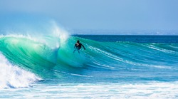 Uluwatu Bali, Indonesia - August 26 2014 : Unknown surfer riding a wave on a  beautiful sunny day.