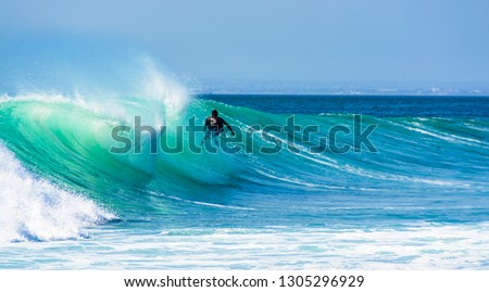 Uluwatu Bali, Indonesia - August 26 2014 : Unknown surfer riding a wave on a  beautiful sunny day. #1305296929
