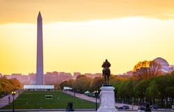 Ulysses S. Grant Memorial statue over National Mall and Washington Monument obelisk with yellow sunset on background