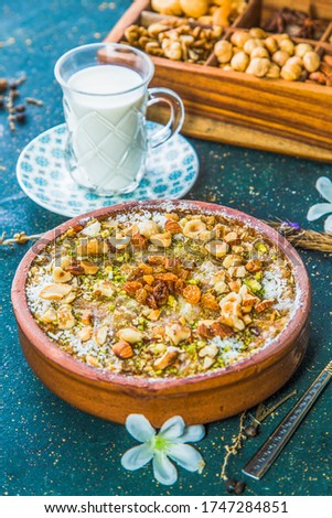 Um Ali dessert with chopped nuts and raisins. Egyptian bread pudding on table with cup of milk and wooden box with nuts. Stock photo ©