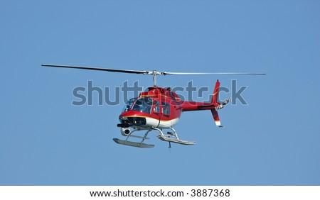 Um helicóptero vermelho brilhante com uma câmera em uma mostra de arda semana da frota em 2006. Pouco borrão de movimento nas lâminas derotor - stock photo